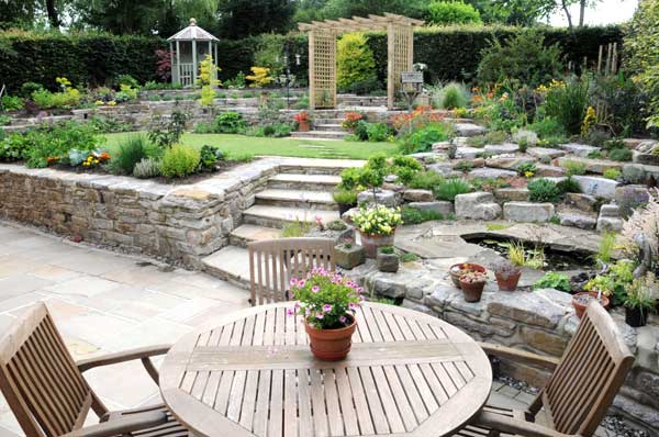 Natural Stone Paved Patio Area And Planted Rock Outcrop With Wildlife Pond.